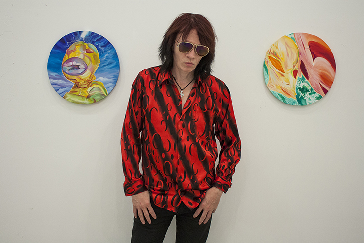 Nick Zedd next to one of his paintings